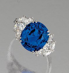 SAPPHIRE AND DIAMOND RING.  Centring on a cushion-shaped sapphire weighing 10.23 carats, the shoulders embellished with pear- and marquise-shaped diamonds, mounted in platinum