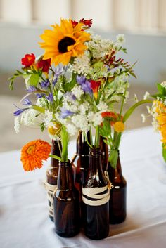 #DIY beer bottle vase centerpieces. Just wrap with twine or jute!---I would do this just the clear bottles that are painted to possibly match colors or have ribbon or such.