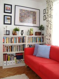 living room red sofa in front of window bookshelves and artwork on wall
