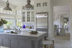 Gray kitchen cabinets, white marble counters, open, bright, two separate sinks, lots of windows, light colored floor, very neutral. http://urbangrace.com/