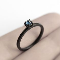 Oxidized sterling silver ring with a round cut dark blue sapphire from Sri Lanka. The stone is set upside down, wrapped with 4 prongs keeping it...
