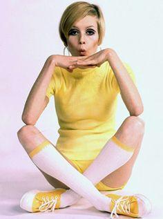 Usando um vestidinho amarelo, meias 3/4 brancas com barra amarela e tênis amarelo com branco.