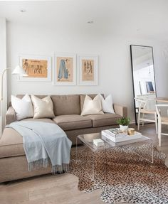 Welcoming living room boasts three framed vintage pattern art pieces mounted to a white wall above a taupe sofa with a chaise lounge accented with champagne metallic pillows, white pillows, and a light blue throw blanket, while a CB2 Peekaboo Acrylic Coffee Table sits in front of the sofa on a cheetah print cowhide rug.