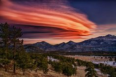 This spectacular, multi-hued formation of so-called lenticular clouds was observed over Rocky Mountain National Park, near Estes Park, Colo. Professional photographer Richard H. Hahn snapped the magnificent view soon after sunset at 5:02 p.m. MST (7:02 EST) on Jan. 5.    Lenticular clouds form when waves of moist, fast-moving air are pushed upward by winds and ascend over high mountains. At the mountain's higher altitude, the moist air's water droplets cool and expand, and the water vapor conden