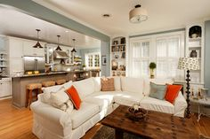 A modern country kitchen/ living room with counter height bar stools with wicker seats, a white sectional sofa and a rustic wood coffee table