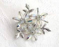 Vintage Aurora Borealis clear crystals brooch, 3 flowers, silver pressed metal leaves, large crystals with silver pin heads, circa 1950s by…