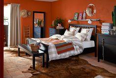 Makuuhuone, jonka seinät on maalattu oransseiksi. Huoneessa puiset IKEA-makuuhuonekalusteet ja lattialla lehmäntalja.