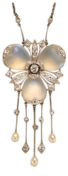 A Delicate Diamond and Moonstone Platinum Pendant. A delicate platinum pendant in the shape of a flower set with three heart shaped cabochon cut moonstone petals and brilliant cut diamonds at the end of the petals and in between them, under the flower are five drops decorated with pearls and diamonds, England, circa 1910.