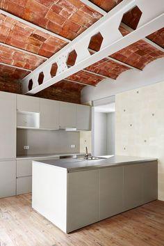 #reforma #cocina (presupuestON.com) abierta con muebles color gris, península para fregadero, techos con bóvedas de ladrillo y vigas de acero vistas, suelo de parquet.