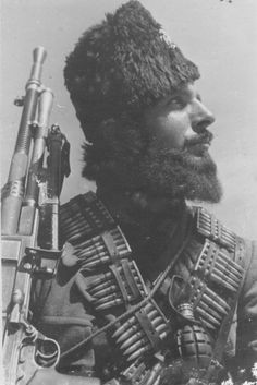 "~~} ""Heavily armed Chetnik fighter poses for the photographer. The Chetniks were Serbian monrachist paramilitaries who collaborated with the Axis at various periods during WW2. They fought, among others, Marshal Tito's communist partisans. After the war, the communist government of federated Yugoslavia banned the Chetniks and hanged several of their senior leaders, including Draža Mihailović, the main architect of collaboration with the Germans."""