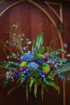 Large Altar arrangements for peacock themed wedding using Greenery, hydrangea, orchids, feathers, curly willow. At Le Beaux Chateau in Flower Mound, Texas. Wedding flowers by Rosie's Floral Boutique. Photography by Cherie Callaway.