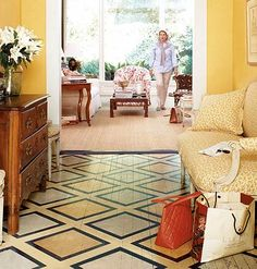 An entryway with a detailed painted floor design in a square pattern. Wood floor and a painted