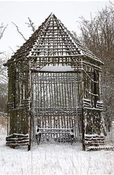 Rustic wooden gazebo and bench covered in snow