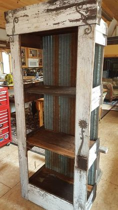 Custom-made reclaimed barn wood door, rustic distressed flaking paint siding, rusted corrugated roo