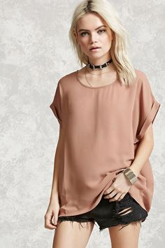 A sheer woven top featuring short cuffed sleeves, a round neckline, and a flowy silhouette.