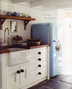 Blue fridge, rustic shelving and traditional 30s sink