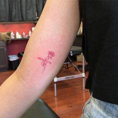Red ink rose tattoo on the right inner arm.