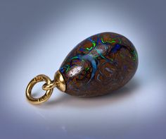 A Strikingly Beautiful Gold Mounted Carved Boulder Opal Antique Russian Miniature Egg Pendant. This highly unusual egg was made in St. Petersburg between 1908 and 1917 by jeweler W. Warburton, a UK citizen, supplier of the Russian Imperial Court. Jewelry by Warburton is extremely rare today. Clearly, this gold mounted carved egg was influenced by Warburton's neighbor - Peter Carl Faberge, whose shop was at B. Morskaia No. 16, and after 1900 - at B. Morskaia No.24.