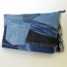 One-of-a-kind. Convenient and stylish. Pretty cool recycled jean patchwork clutch bag. A bag is made from old Jeans and denim fabric. Fully lined with pockets: 3 x inside, 2 x outside. Zipper top closure. The bag can be held by placing the thumb in a loop.  Zipper slider : denim tassel with a chain and beads. (Gold)  Material: old jeans and hand-woven (hand-dyed indigo denim). Color: dark indigo, indigo, blue & light blue. Size: 8 H x 12 1/2 W x 1 1/2 D