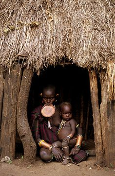 Surma mother and her baby sit in their small hut. Kibish river- Sudan / Ethiopia border/Boaz Rottem