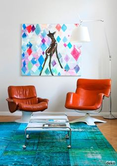 12 White Rooms with Pops of Color: An of-the-moment over-dyed rug (so oceany!) sets a saturated stage for two vintage leather armchairs in this living room sourced from Finnish pub Scandinavian Deko. The whimsical artwork takes the almost serious space down a notch.