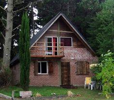 Fachada campestre de ladrillo visto con detalles en madera y ventanales simples con naturaleza a su alrededor.
