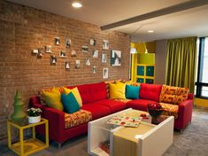 A red sectional with a few patterned cushions add an interesting piece on its own, but it is dressed up by blue, yellow and green throw pillows in this eclectic living room. A brick wall gives the space an urban vibe, and a white contemporary coffee table anchors the room.