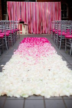 Silver chairs with pink cushions. Ombre pink petal path. Pink streamer backdrop. Pink perfection