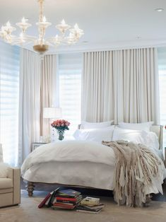 White on white fabric radiates a glamorous hollywood feel in this dreamy master bedroom. Textural elements, such as the chunky throws and striking chandelier, add depth to the space.