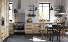 Cocina grande de fresno con tiradores negros y encimeras blancas, acabada con un horno microondas, una cocina y un extractor de acero inoxidable.
