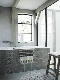 Black and white bathroom with bath, knitted carpet and wooden stool Laundry In Bathroom, White Bathroom, Grey Bathrooms, Small Bathroom, Modern Bathroom Design, Bathroom Interior Design, Bathroom Designs, Bathtub Tile, Beton Design