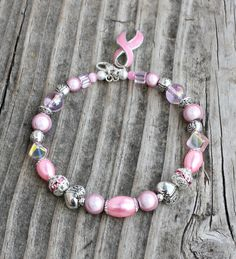 Pink Breast Cancer Awareness Bracelet $16.00  What better way to show your support for breast cancer awareness than with this pretty pink bracelet!  It is made with glossy round glass beads, round miracle beads (glow in certain lighting), glass pearls in teardrop and oval shapes, glass cubes, cat's eye rounds, silver stardust spacers, tibeta...