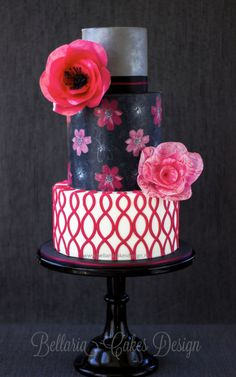 Fun and elegant, this cake has pretty, hand-painted cosmos, a silver tier, that lovely hot pink pattern (trellis pattern, very on trend) and big, showy wafer paper blooms.
