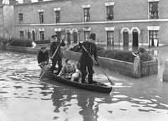 13th March 1947: Policemen in a rowing boat rescue inhabitants of Spring Lane, Clapton, London, where flood waters have reached alarming heights after the River Lea burst its banks.