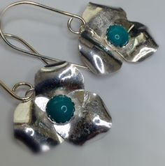 Organically formed, hand forged argentium sterling silver earrings with a 6 mm turquoise cabochon. The flowers measure approximately 15/16 x 15/16 of an inch and hang approximately 1.5 inches down from the ear. shiny silver finish!