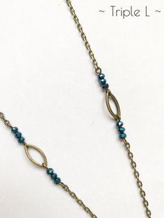 ~ DESCRIPTIF ~ Ce collier sautoir est composé dune chaîne bronze avec breloques navettes en bronze et perles à facettes bleues captant la lumière. Il est ajustable grâce à une chaînette en bronze. La chaînette mesure 5 cm. Dimensions du collier : 41 cm de long.  ~ MATERIEL UTILISE ~ - Chaîne couleur bronze - Fermoir et chaînette couleur bronze - Breloques couleur bronze - Perles à facettes couleur bleue  ~ ENVOI ~ Les bijoux sont envoyés en courrier suivi dans une enveloppe en papier bulle…