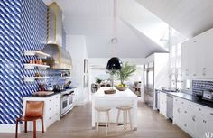 At a Southampton, New York, retreat renovated by interior designer David Netto and architect David Hottenroth, tiles custom made by Tile Guild based on Gio Ponti designs animate the kitchen, which is appointed with pendant lights by Schoolhouse Electric & Supply Co., a hood custom made by RangeCraft, a Sub-Zero refrigerator, a Wolf range, and a pair of BassamFellows tractor stools from Design Within Reach.