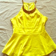 Yellow top Make a statement when you show up in this beautiful canary yellow, sleeveless top accented with gold neckline. Size M. Worn once Tops Tunics