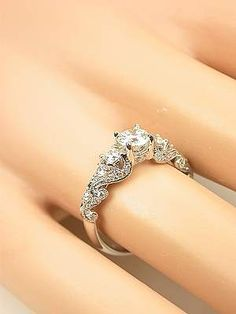 Very pretty band with a much bigger diamond in the center. Sometimes all the bling on a band becomes so expensive that the middle diamond is too small and is overpowered by a pretty band. Swirling Diamond Engagement Ring