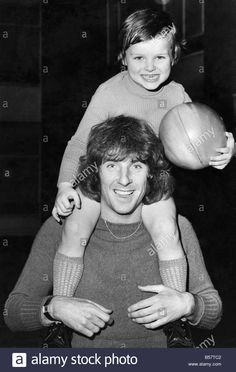Download this stock image: On the eve of London derby game between QPR and Arsenal, Stan Bowles plays with his four year old son Carl at their Wembley, North London home.;October 1977 ;P003862 - B57TC2 from Alamy's library of millions of high resolution stock photos, illustrations and vectors.