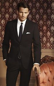 A beautifully fitted black suit on a very handsome man!