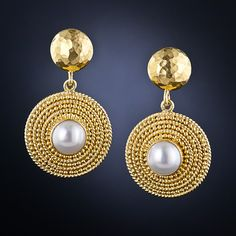 Ancient-style drop earrings featuring a lustrous button pearl centered amid concentric granulated circles surmounted by hand-hammered tops in rich 18 karat yellow gold by the renowned Grecian jewelsmith - Ilias Lalaounis.