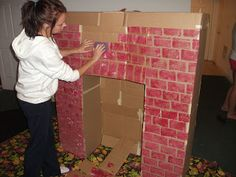"Make your own cardboard fireplace! Use a sponge to make the ""bricks."""