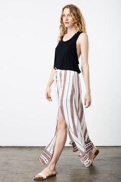 "This skirt features an ethnic printed fabric and two high front slits that won't restrict your movement, resulting in a very comfortable maxi skirt that is perfect for almost all of your summer resort activities.  Fabric: 100% Cotton Color: Ivory & Red Sizing: Standard Women's US Sizes  Model in: Size S Model Measurements: Height 5'10"", Waist 24"", Bust 34"", Hips 34"" Style: Beach Skirt, Maxi Skirts, Double Slit  Garment Care: Delicate Wash Import   About the Designer: Wilde Heart With it..."
