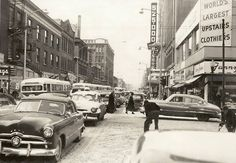 Snowy day, Downtown Des Moines, 1953. View is of 7th Street and Locust looking west. United Federal Savings and a row of Curbliners are on the south side of the block. Foreman & Clark mens store is above Fanny Farmer Candies. Bishop's Cafeteria and DM Register & Tribune [525-000, number of Sunday subscribers] are on the north side of the street.