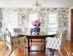 The dining room, lined in a Fromental wallpaper, features a George III oak table ringed with chairs designed by Adam Otlewski and custom made by Cotton.