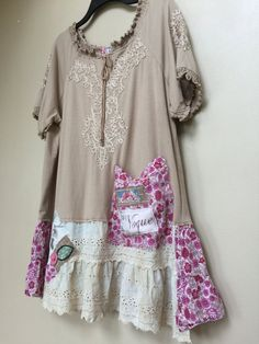 Cute Romantic Shabby Chic Patchwork And Appliqué Tunic, pretty Ruffled Elastic Sleeves , And Ruffled Neckline. Soft Tan Jersey Knit With added Pink Floral Skirting and Pocket with artsy fabric Rose. Size XL to 1X Measured taken laying flat- 23 across armpit to armpit So a Bust up to 45-46 33 long measured from top of shoulder to Hemline Adorable to wear with leggings or jeans