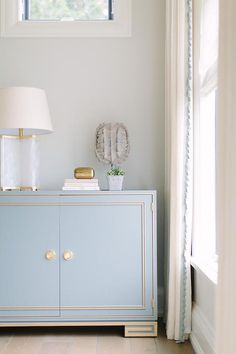 Blue and gold foyer features a French blue cabinet with gold trim and ring pulls topped with a ...