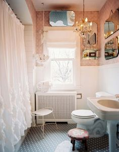 Oh what's not to love in this girly bathroom? Love the white ruffle curtain, the hanging towel basket, mirror wall and chandelier! Would love to recreate this in my master bath!