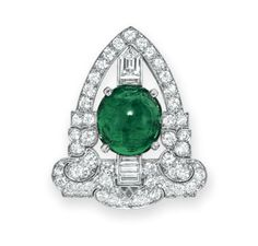 AN ART DECO EMERALD AND DIAMOND CLIP BROOCH, BY TIFFANY & CO.   Set with an oval cabochon emerald, within a circular and baguette-cut diamond geometric frame, mounted in platinum, circa 1925  Signed Tiffany & Co.